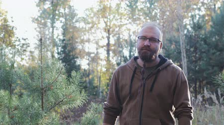 haver : Brutal, bearded, bald man with glasses goes to the camera forward against the autumn forest Stock mozgókép