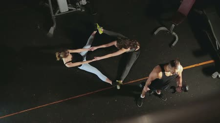 flexão : Girls athletes do stretching on the floor in a couple in the fitness room, the guy bodybuilder lifts the dumbbell, shakes biceps. A group of people engaged in fitness Stock Footage