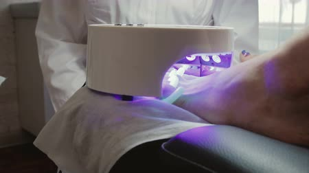 kurutma : Nails on the clients foot are dried under the lamp after applying the gel Polish. Hardware pedicure in the beauty salon. Concept of beauty