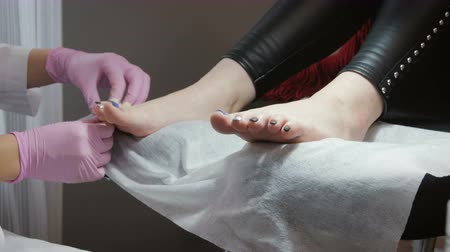 painless : Master pedicure with gloves shares the toes of the client with a special device, a beauty salon