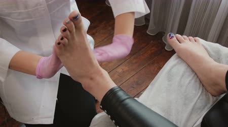 masszírozó : The masseuse in sterile, clean clothes puts cream on her hands and makes a foot massage to her client