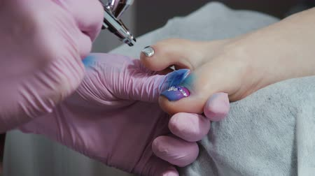 pulverizador : Manicure in pink gloves paint the toe nails airbrushed at the salon. Blue nail Polish and rhinestones. Beautiful and rich pedicure Vídeos