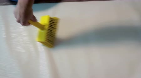 склеивание : Close-up of the hand of a man applying glue to the Wallpaper with a yellow brush. The concept of preparation for the repair of premises