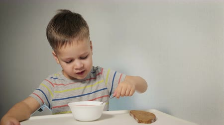 barszcz : Small, funny kid eating at the table, biting a piece of bread, hungry kid