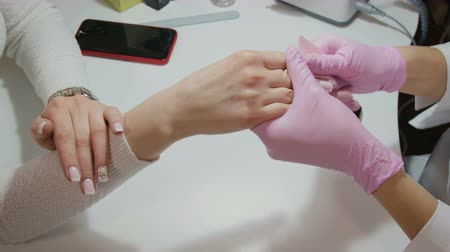 tırnak : Manicurist with gloves and wipes and polishes with a special cloth painted nails client Stok Video