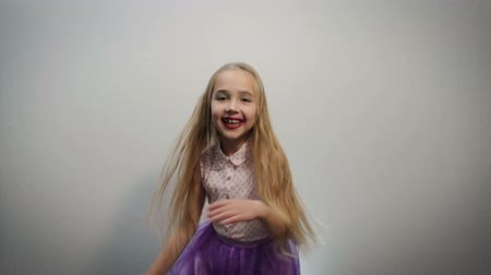 sprung : Dreamy, little girl with funny makeup on her face dancing, jumping and posing in the Studio. Romantic expression. Happy child concept Videos