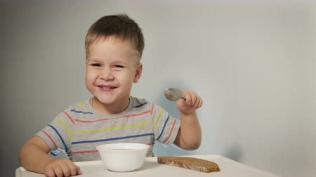 níveis : A cheerful, naughty child laughs and waves his head, he sits at the table over a plate of half-eaten soup, does not want to eat healthy food