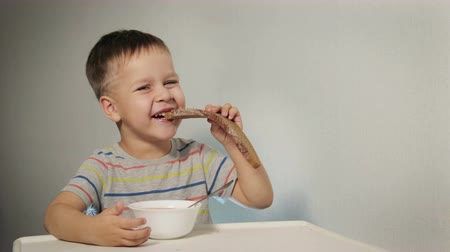 níveis : Cheerful, mischievous child laughs and bites bread, sitting at the table over a plate of half-eaten soup, does not want to eat healthy food Stock Footage