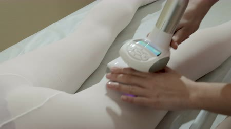 masajista : Close-up of a pretty Caucasian woman in a white protective jumpsuit on an LPG massage in a beauty salon. The hands of a specialist moving the device through the body of the patient. Steadicam shot