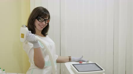 салоны красоты : Portrait of a friendly Caucasian woman doctor, beautician in white overalls and goggles, gloves, with a device for laser hair removal in his hand. Concept: painless procedure