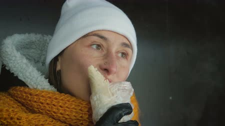fast food : Cute, hungry girl in a white hat and a yellow scarf eating a sandwich. Fast, harmful nutrition Stok Video