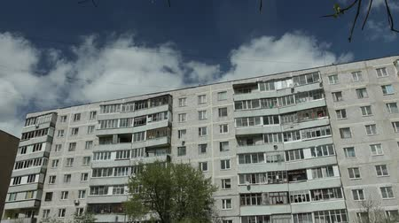 arame : Timelapse of former clouds in the blue sky, floating on the background of an apartment building. Concept of poverty and poverty of ordinary Russian citizens