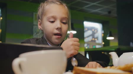 łyżka : Funny schoolgirl 7-8 years in uniform eats a cake with a spoon in a cafe during lunch, Breakfast and looks at the smartphone, tablet Wideo