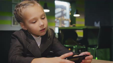 kupa : Funny girl 7-8 years old in school uniform uses a smartphone, tablet computer in a cafe Stok Video