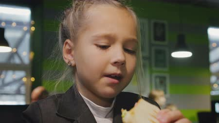 kupa : Funny schoolgirl 7-8 years eats cake in a cafe during a break before classes