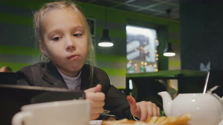 kupa : Funny schoolgirl 7-8 years in uniform eats a cake with a spoon in a cafe during lunch, Breakfast and looks at the smartphone, tablet Stok Video