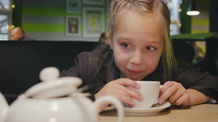 kupa : Close-up of a funny girl in a school uniform, drinking tea in a cafe. The child looks at the smartphone, tablet in the foreground