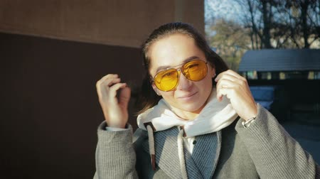 позирует : Portrait of an adult, a girl in a coat and yellow glasses, who smiles happily in the fresh air. The woman froze and put on the hood, its cold outside Стоковые видеозаписи