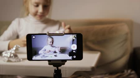 tojás : A static frame of a lovely baby girl in a white jacket unpacking an egg with a surprise. Young blogger writes a video for publication and likes in home Studio Stock mozgókép