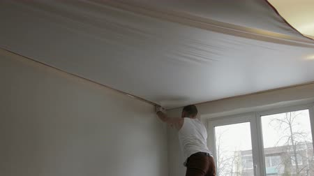 naprawa : Static General plan of a young man installing a canvas of white stretch ceiling in the room of the apartment Wideo