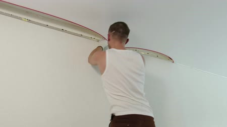 installer : Static medium shot of a male worker in a white t-shirt is to mount the suspended ceiling in the room of the apartment