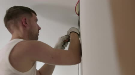 installer : Static close-up of a male Builder in a white t-shirt mounting a stretch ceiling in the apartment