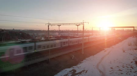 mozdony : Top view of the high-speed train passing in the winter against the backdrop of a picturesque sunset (rising) sun. 4k