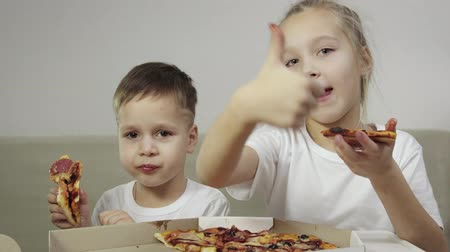 doigts : The average plan of two lovely, funny children eating pizza. The boy smiles, the girl laughs and shows her finger like. Concept: delicious Breakfast, lunch, dinner, treats.
