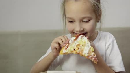 mókás : Close-up of babys hand taking a piece of juicy, greasy pizza and bringing it to her mouth, funny girl in white t-shirt tries the treat, licks and smiles. Unhealthy food concept. 4K resolution