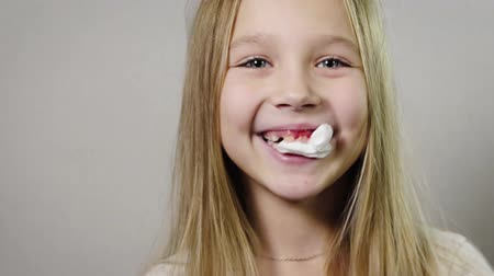 зубы : Portrait close-up of a cute smiling girl, a child with a white napkin in his mouth, bleeding gums, jaw. Tooth loss by age concept. 4K resolution