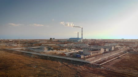 výfuk : Top view of a small industrial enterprise with smokestacks standing in a field against a blue sky and clouds. The camera slowly flies up to the plant. 4K resolution