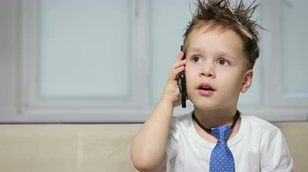 mókás : A small, handsome boy with a stylish hairstyle and a blue tie is talking on the phone. Joyful and happy baby, little boss