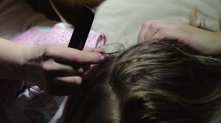 lice : Mom cleans her daughters hair from nits and lice with a special comb, combs insects from the head. Concept childrens head lice