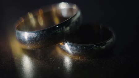 объект : Two gold wedding rings on a dark background under a direct beam of light cast highlights and shadows. The concept of the celebration