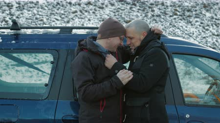 beira da estrada : Two LGBT guys, bald with a beard and wearing glasses and a hat hugging and chatting on the side of the road near the car. The journey of homosexuals. 4K Stock Footage