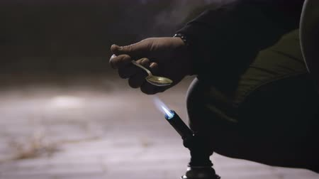 alışkanlık : A young drug addict in a black jacket with a hood warms in a spoon on an open fire of a gas burner chemistry for injection into a vein. The man shaking hands from withdrawal, close-up