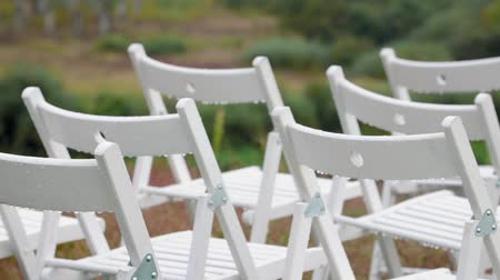 gramado : Panorama of the variety of white folding chairs in the area of marriage registration at the wedding ceremony with drops from the rain. Wet seat in the open air