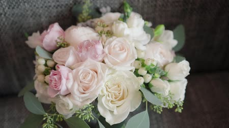 buquê : Panorama of a beautiful wedding bouquet of white and pink roses on the couch in the apartment or Studio Vídeos