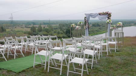otwarte : Steadicam shot of a variety of white folding chairs in the reception area of the marriage on the wedding ceremony with drops of rain. Wet seat under the open sky Wideo