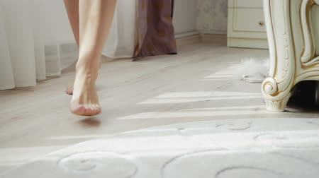 подвенечное платье : Close-up of the legs of a young sexy European bride girl matching a white wedding dress in a luxurious boudoir room