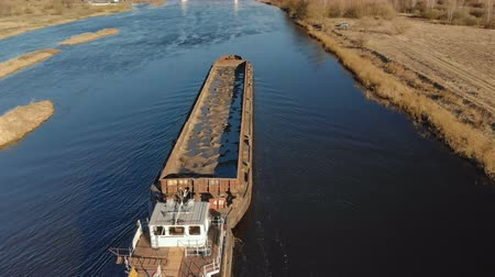 фарватер : Aerial shot of a tug ship with an empty barge floating on the river in spring. 4K resolution