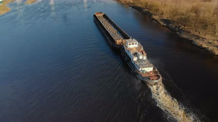 plachta : Aerial shot of a tug ship with an empty barge floating on the river in spring. 4K resolution