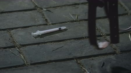 dose : Close-up of a rubber tourniquet falls near the syringe on the paving slabs. The concept of drug dependence