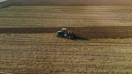 solo : Aerial shot of a blue tractor cultivating brown earth in Sunny spring, autumn weather. The concept of the beginning of the sowing season in agriculture