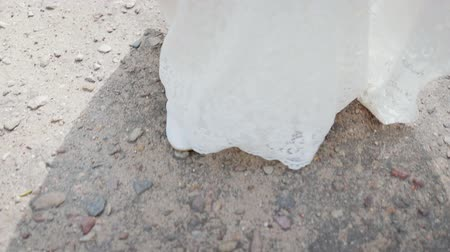 noiva : Close-up of the feet of a young bride in white shoes and a long wedding dress walking on the rocky pavement. The concept of the road of family life