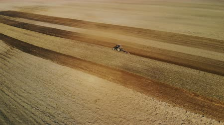 poeira : Aerial view of the tractor with the agricultural unit performs the plowing, the cultivation of the soil of brown color in the dry Sunny weather. Bad harvest concept Vídeos