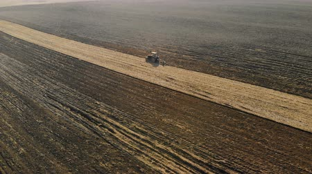 мрачный : Aerial view of the tractor with the agricultural unit performs the plowing, the cultivation of the soil of brown color in the dry Sunny weather. Bad harvest concept Стоковые видеозаписи
