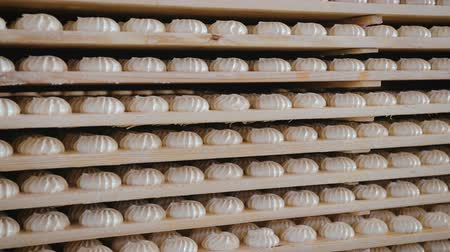 klaar : Panorama of many sweets white marshmallows stored in wooden racks in the warehouse of the confectionery factory. The concept of ready-made sweet products
