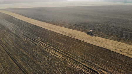 tırmık : The farmer tills the soil on the tractor, the beautiful landscape of ploughed, cultivated fields. Birds-eye view