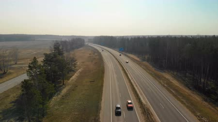 ciężarówka : Top to bottom.Different vehicles are moving on a busy highway. Flying over cars and trucks that drive on a busy highway passing through autumn nature. Wideo